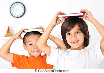 Happy cute boys at home, lovely little brothers with books on heads