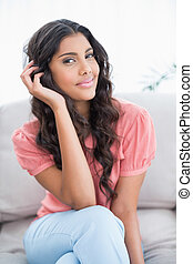 Happy cute brunette sitting on couch posing