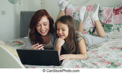 Happy cute daughter and young mother have online video call with father or grandmother using laptop computer lying on bed in cozy bedroom at home