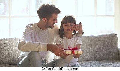 Happy cute daughter receiving gift box from loving father embracing