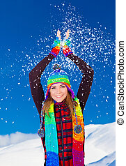 Happy cute girl playing with snow outdoor