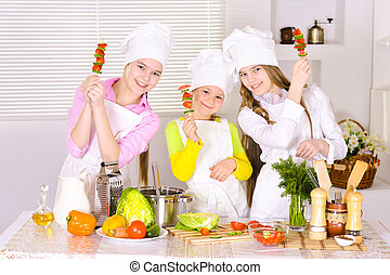 happy cute girls cooking vegetable dish on kitchen