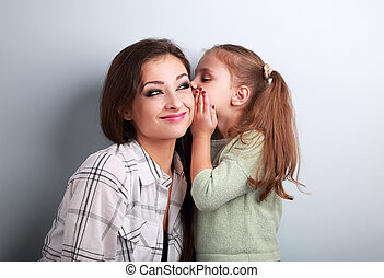 Happy cute kid girl whispering the secret to her funny grimacing mother in ear in studio on blue background