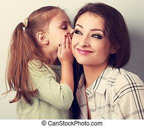 Happy cute kid girl whispering the secret to her funny grimacing mother in ear in studio. Toned closeup portrait