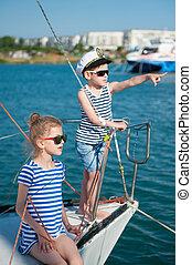 happy cute kids aboard luxury yacht in summer sunny day in port
