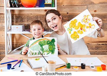 Happy cute little boy and his mother showing their paints -...