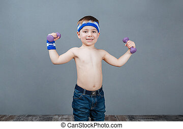 Happy cute little boy standing and doing exercises with dumbbells
