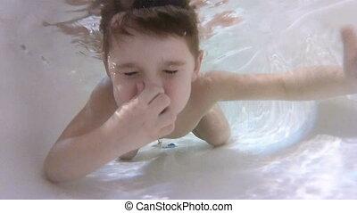Happy cute little boy underwater