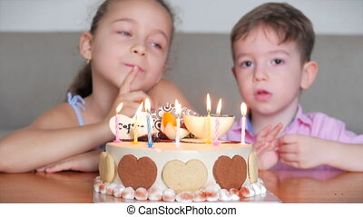Happy cute little girl and her little brother sitting on the sofa making a wish for their birthday, celebrating birthday with family, making a wish and blowing out the candles on the cake.