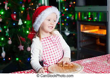 Happy cute little girl in the kitchen baking gingerbread