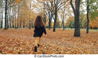 happy cute little girl with curly hair runing through the...
