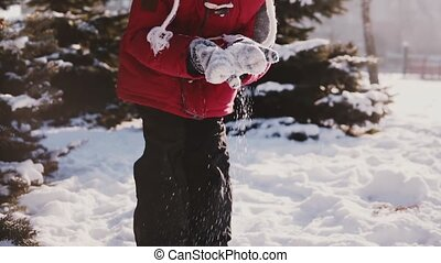 Happy cute playful little Caucasian girl in winter clothes looking at camera then throwing snow in the air slow motion.