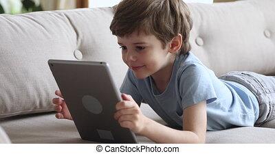 Happy cute preschool boy using tablet lying on sofa alone