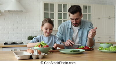 Happy cute small daughter cooking with father looking at camera