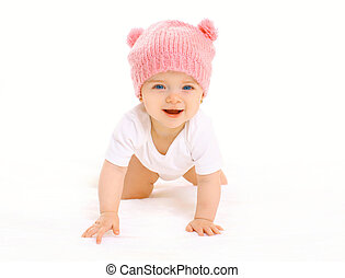 Happy cute smiling baby in knitted pink hat crawls on white background