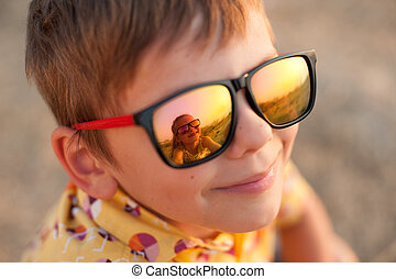 happy cute smiling boy in sunglasses with reflection of beautiful little girl in summer sunset day