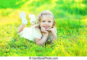 Happy cute smiling little girl child lying on grass in sunny summer day