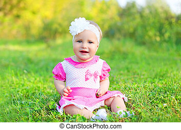 Happy cute smiling little girl child sitting on grass in summer day