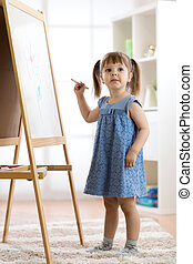Happy cute toddler girl drawing or writting with marker pen on a blank whiteboard at home, preschool, daycare or kindergarten