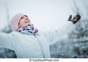 Happy Cute Woman Enjoying Winter during a Snowy Day