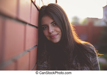 Happy cute woman leaning on the brick wall