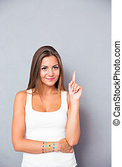Happy cute woman pointing finger up and looking at camera ...
