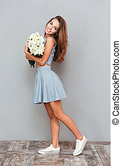Happy cute young woman standing and holding bouquet of flowers