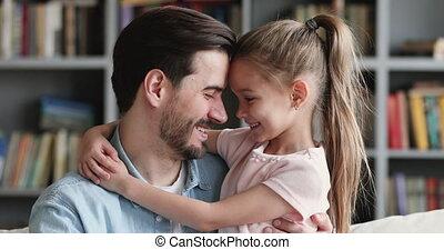 Happy dad and cute kid daughter cuddling looking at camera