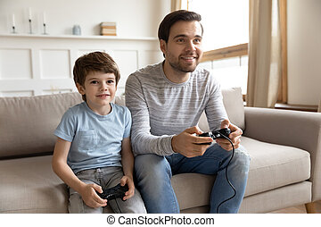 Happy dad and preschooler son play computer games together