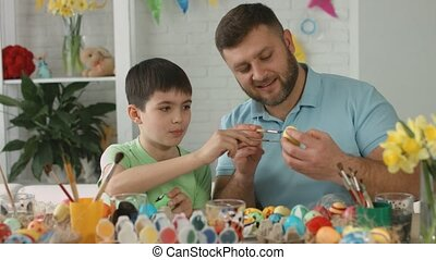 Happy dad and son paint eggs for Easter