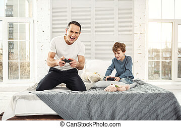 Happy dad and son playing games