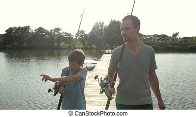 Happy dad and son with rods going fishing on pond - Joyful...