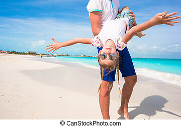 Happy dad have fun with his little cute girl during beach vacation