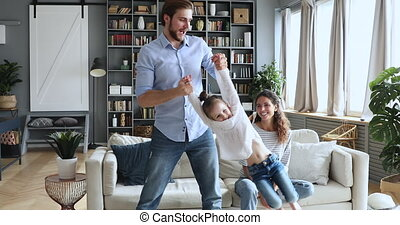 Happy dad lifting cute daughter having fun on family weekend