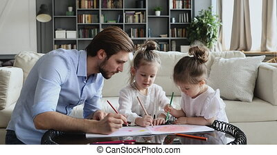 Happy dad playing with adorable daughters drawing at home table