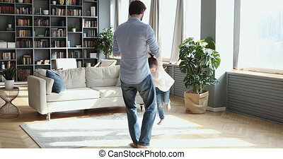 Happy dad playing with daughter having fun in living room
