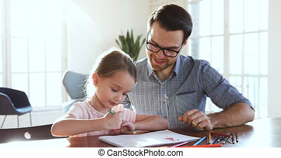 Happy dad teaching little cute girl drawing with colored pencils