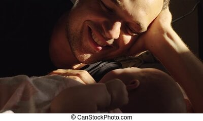 Happy dad with baby who starts crying