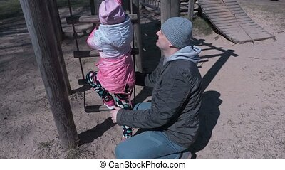 Happy dad with daughter on the playground