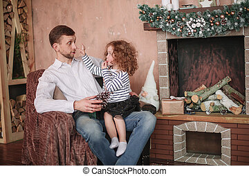 happy dad with his little daughter sitting in a cozy living room.