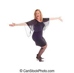 Happy dancing woman in black dress.