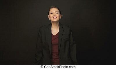 Happy dancing woman in black jacket