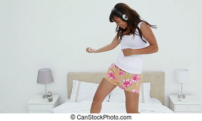 Happy dark-haired woman playing air-guitar