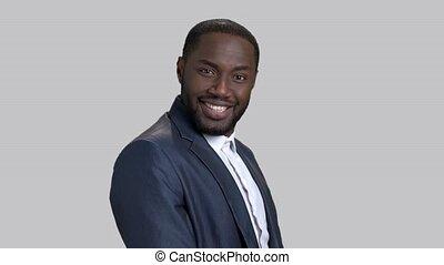 Happy dark-skinned businessman on grey background. Surprised...