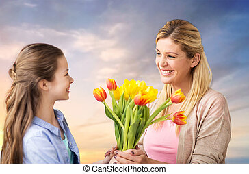 happy daughter giving flowers to mother over sky