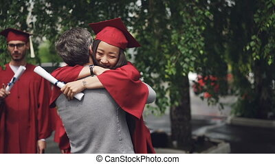 Happy daughter graduating student is embracing her loving...