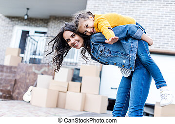daughter piggyback riding mother - happy daughter piggyback...