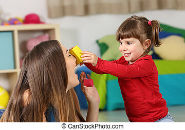 Happy daughter playing with her mother
