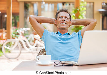 Happy day dreamer. Relaxed mature man holding hands behind head and smiling while sitting at the table outdoors with laptop on it