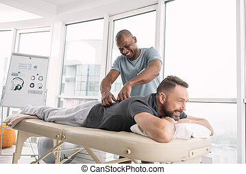 Happy delighted man doing a massage